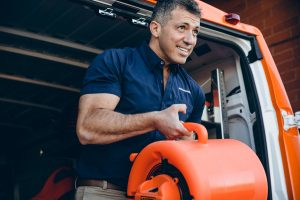 water damage restoration expert takes air mover out of van