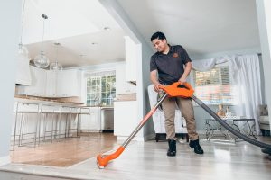 water damage restoration technician vacuums water in house