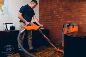 commercial water damage restoration technician vacuums water in office