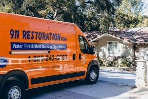 911 Restoration orange van parked in driveway of house
