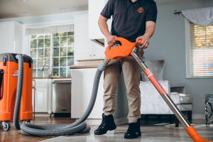 water damage restoration technician extracting water from home