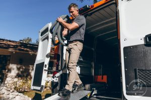 commercial water damage technician carries equipment out of vehicle
