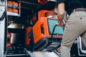 technician rolls equipment into van